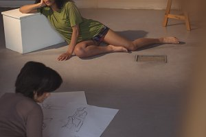 Female artist drawing a sketch of woman on paper