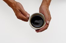 Hands holding black coffee cup