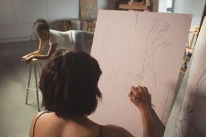 Female artist drawing a sketch of woman on canvas