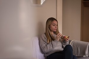 Young woman having fruits on sofa