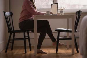 Low section of woman using laptop at table