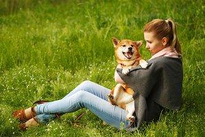 Girl hugs dog Shiba Inu.