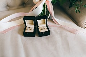 Silver wedding rings with gems in a beautiful black boxes on the piece of the ribbon. Close-up. Artwork