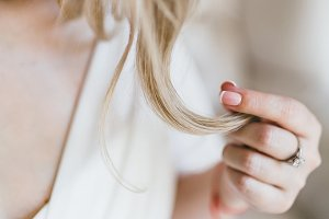 Close up image of beautiful bride holds a earlock. Soft focus on a strand of hair. Artwork