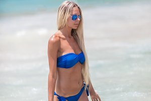 blond woman in blue bikini on white tropic beach
