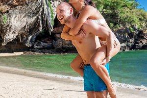 boyfriend carrying his girlfriend tropic beach