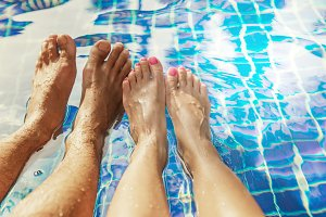 Legs of a couple swimming pool man woman