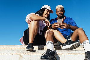 Mixed race friends using mobile.
