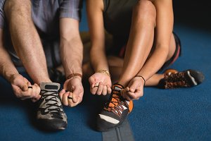 Low section of athletes tying shoelace while sitting in gym