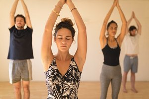 Yoga instructor with students mediating while standing in studio