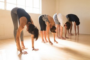 Yoga instructor with students exercising in studio
