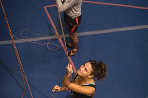 Athletes holding ropes while climbing in gym