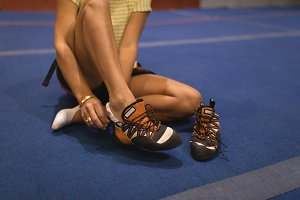 Low section of female athlete wearing shoes in gym