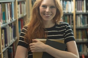 Beautiful woman holding books in library