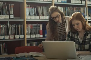 Female friends using laptop in library