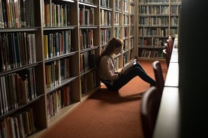 Woman reading book in library room