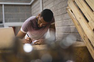 Man writing in diary while sitting at coffee shop