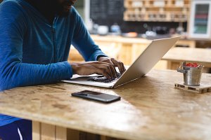 Midsection of young man using laptop in coffee shop