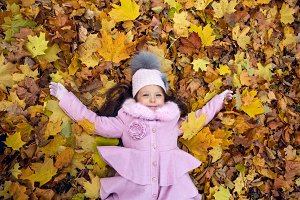 baby girl lying on autumn leaves in pink coat