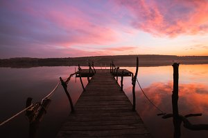 Perspective view of a wooden pier on a river at sunset