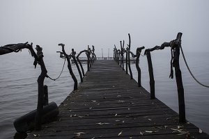Wooden pier on the lake. Fog