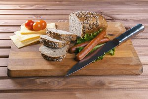 Fried sausages on green salad, bread, cherry tomatoes and cheese on wooden board