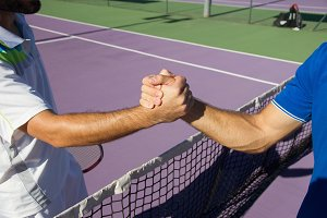 Tennis players holding hands