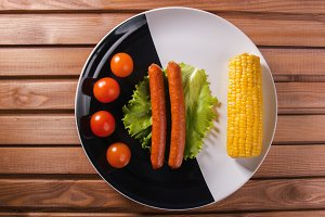 Corn, sausages and tomatoes on the plate at wooden table