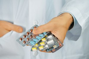 This will help. Doctor holding Different blisters with colorful pills, close-up