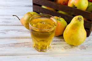 Glass of juice with ripe apple