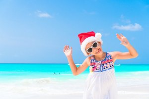 Adorable little girl in Santa hat during Christmas beach vacation. Little kid at Christmas beach holidays