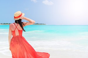 Young woman in hat during tropical beach vacation. Back view of girl