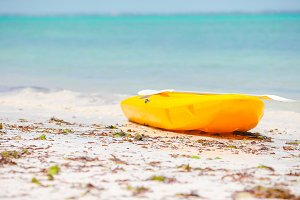 Small boat on the white sandy tropical beach and turquiose ocean