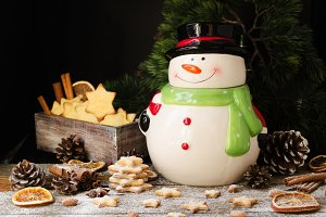 Christmas gingerbread cookies star with a jar of snowman on a wooden table, selective focus
