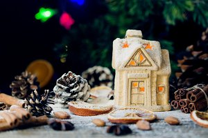 Christmas card with little toy house and decorations on a wooden rustic table, selective focus