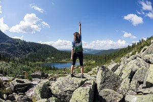 Girl enjoy a beautiful mountain lake, in the Ergaki national park, Russia
