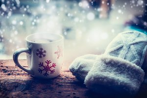 Mug with snowflakes at winter window