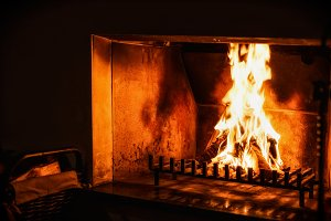 Fire burns in rustic fireplace
