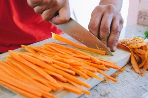 man cooking, cut carrot julienne style