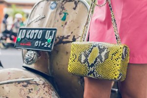 Closeup woman hands with fashion luxury snakeskin python handbag on a retro motorbike background. Outdoors, Bali island.