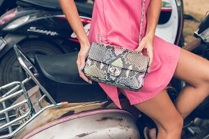 Closeup woman hands with fashion luxury snakeskin python handbag on a retro motorbike background. Outdoors, Bali island.