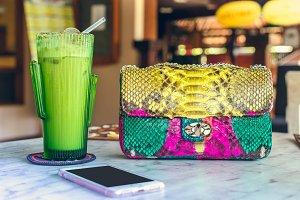 Fashion luxury snakeskin python handbag on the wooden table in restaurant. Bali island.