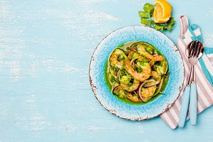 MEXICAN CUISINE. Aguachile de camaron. Prawns aguachile. Shrimps eviche cebiche with cucumber, lemon and purple onion. Top view, blue background