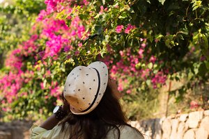 Traveller woman enjoying the view of blossoming bouganvilea
