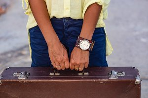Closeup of woman hands holding vintage suitcase