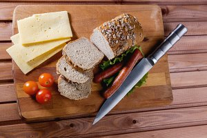 Fried sausages on green salad, bread, cherry tomatoes and cheese on wooden board, top view