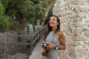 Travelling woman holding vintage camera in her hands and smiling