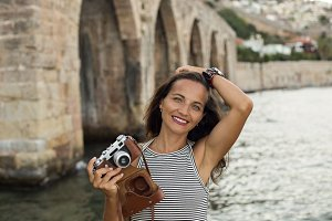 Smiling traveller woman with vintage camera