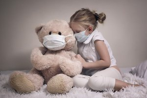 Girl and plush bear in medical masks