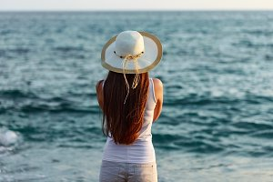 Young woman in summer outfit and hat by seaside